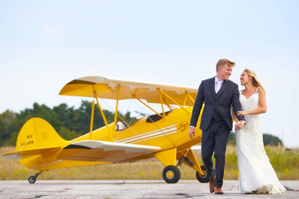 photo of a couple on airport with yellow airplane