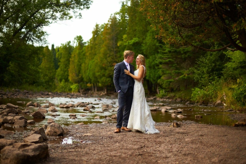 bride and groom in front of the river