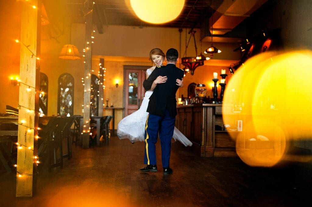 01 bride and groom dancing with lights in warm wood venue