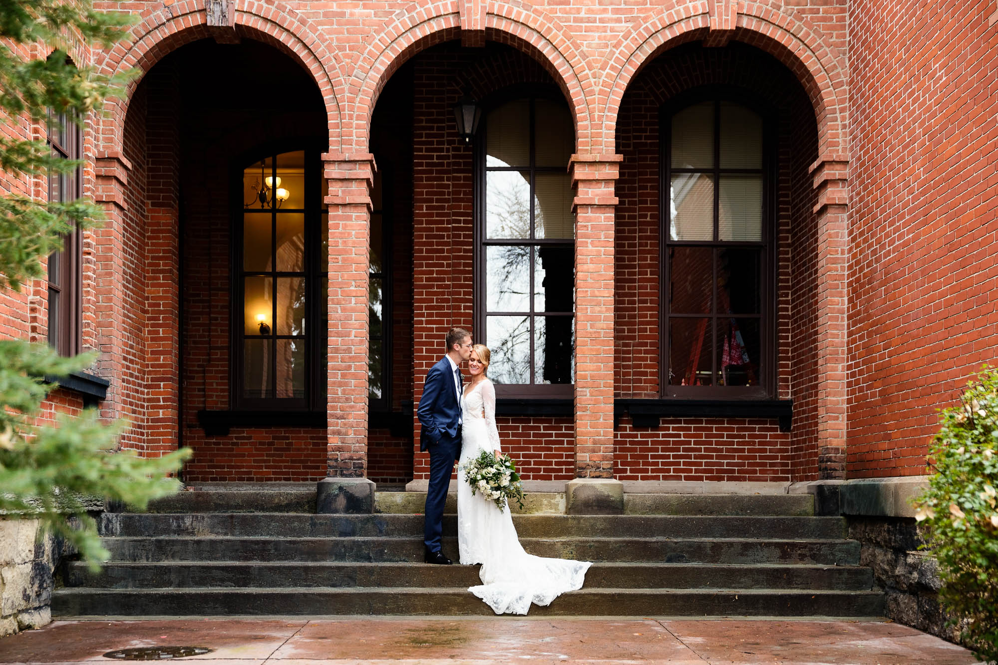 bride and groom standing with brick arches