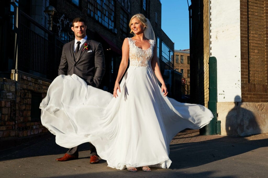 bride playing with her dress in old industiral street