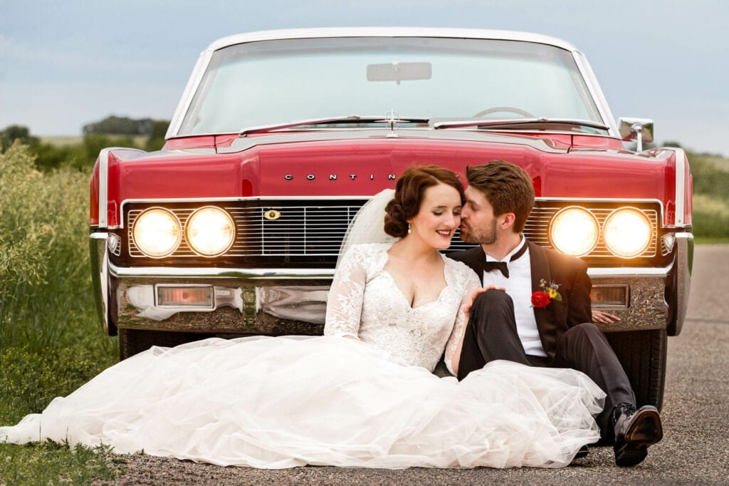 50 couple seating in front of an old american car