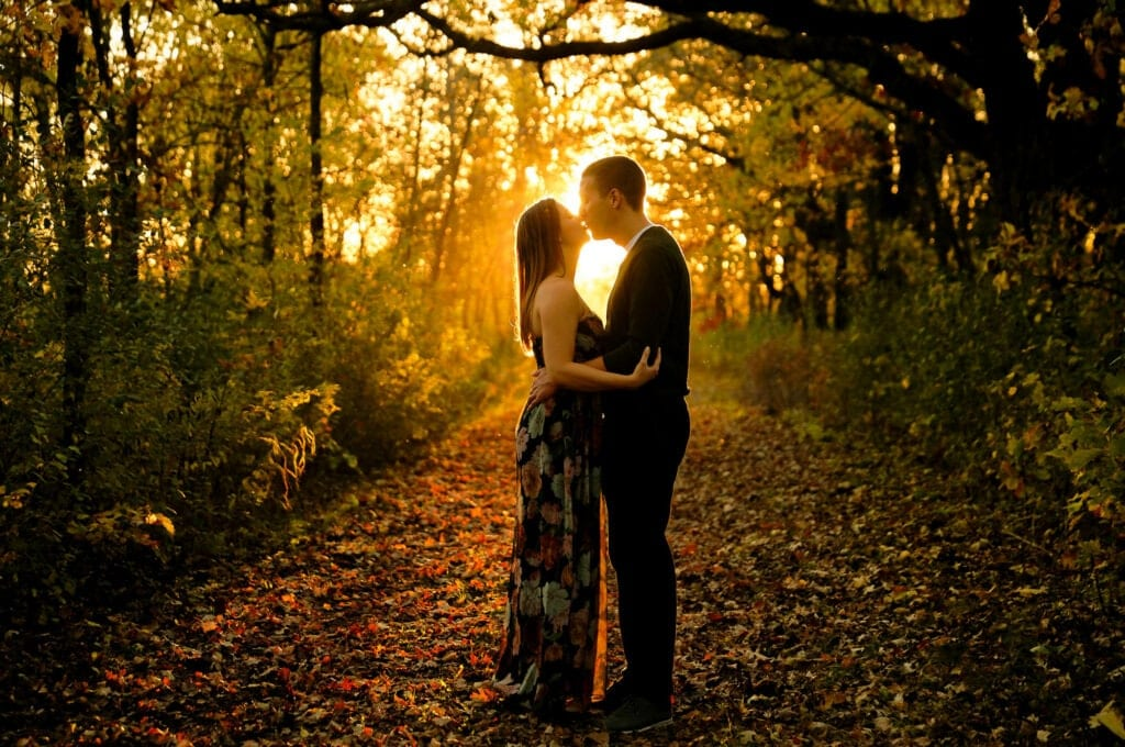 couple in love kissing in the woods falls seasons engagemetn session