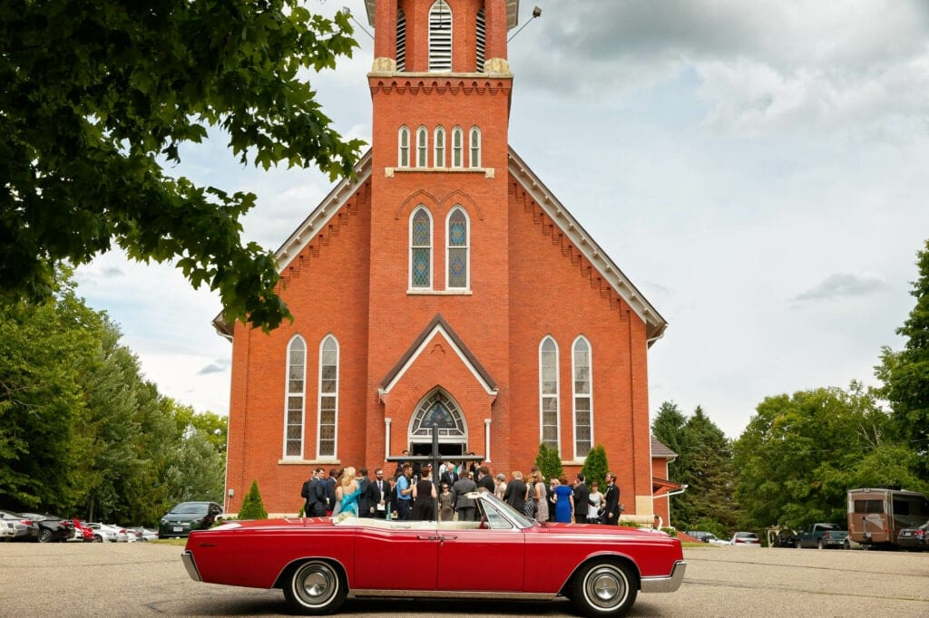 61 red american car in front of a red brick church